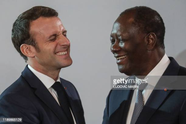 TOPSHOT French President Emmanuel Macron greets Ivorian counterpart President Alassane Ouattara on the sidelines of a press conference at the...