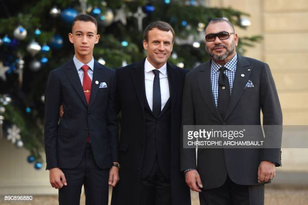 French President Emmanuel Macron greets King Mohammed VI of Morocco and Crown Prince of Morocco Moulay Hassan as they arrive at the Elysee palace on...