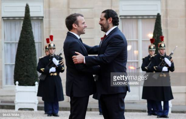 French President Emmanuel Macron greets Lebanese Prime Minister Saad Hariri as he arrives for an official dinner at The Elysee Palace in Paris on...