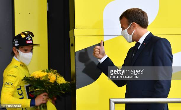 French President Emmanuel Macron greets Team Jumbo rider Slovenia's Primoz Roglic wearing his overall leader yellow jersey on the podium atop the...