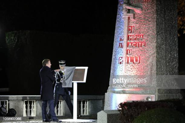 French President Emmanuel Macron helped by a gendarme unveils a plate to pay tribute to the WWI monument of La Pierre d'Haudroy in La Flamengrie...