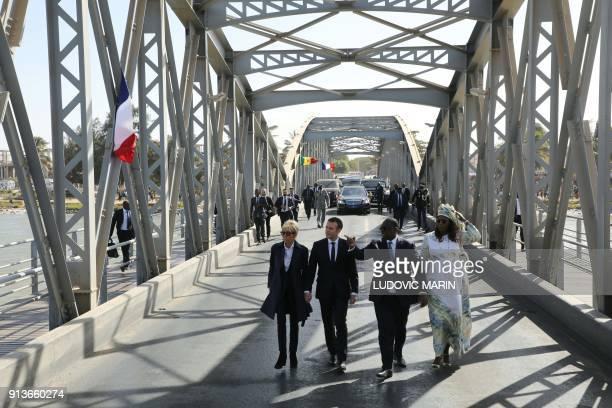 French President Emmanuel Macron , his wife Brigitte Macron and Senegalese President Macky Sall and his wife Marieme Faye Sall walk on a bridge in...
