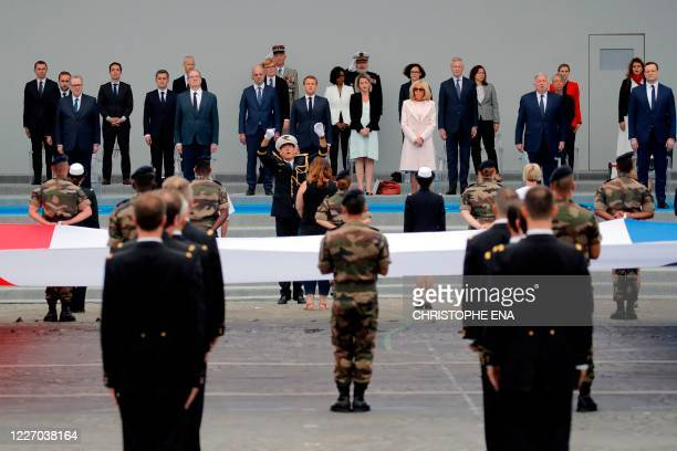 French President Emmanuel Macron his wife Brigitte Macron and members of the French government sing the national anthem attend the annual Bastille...