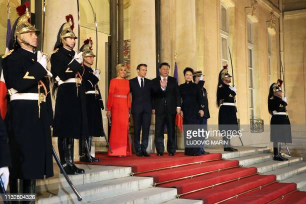 TOPSHOT French President Emmanuel Macron his wife Brigitte Macron Chinese President Xi Jinping and his wife Peng Liyuan pose as they arrive to attend...