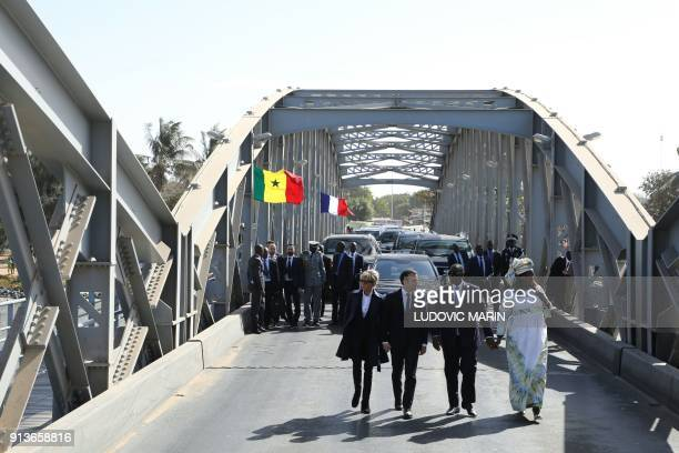 French President Emmanuel Macron , his wife Brigitte Macron , Senegalese President Macky Sall and his wife Marieme Faye Sall wave to the crowd as...