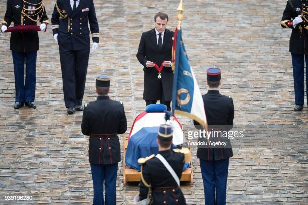 French President Emmanuel Macron holds a medal by the flagdraped coffin of Gendarmerie Officer Colonel Arnaud Beltrame who was killed in last Fridays...