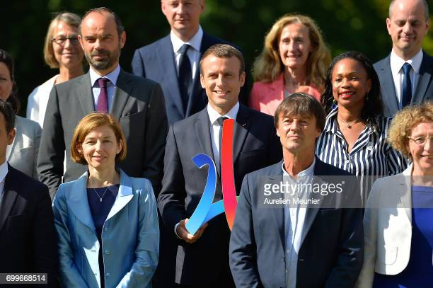 French president Emmanuel Macron holds a Paris 2024 sign as he poses with the members of his governement Prime Minister Edouard Philippe Minister of...