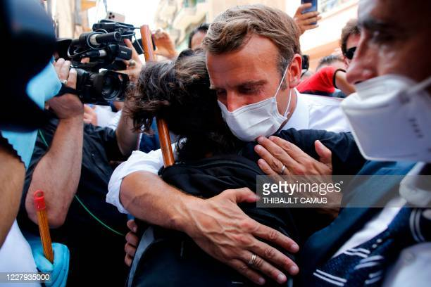 French President Emmanuel Macron hugs a resident as he visits a devastated street of Beirut Lebanon on August 6 2020 two days after a massive...