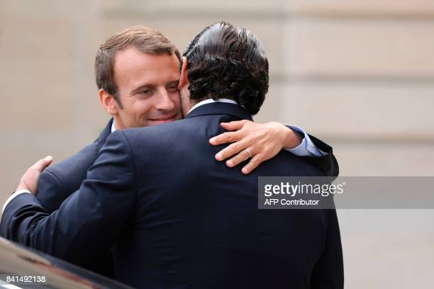 French President Emmanuel Macron hugs Lebanese Prime Minister Saad Hariri after their meeting at the Elysee Palace in Paris on September 1 2017 / AFP...