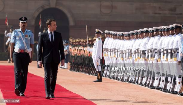 TOPSHOT French President Emmanuel Macron inspects a guard of honour of Indian troops during a welcoming ceremony at Rashtrapati Bhavan The...