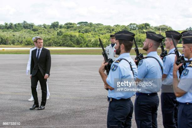 French President Emmanuel Macron inspects a military honour guard upon arrival at the Felix Eboue Airport of Cayenne in French Guiana at the start of...