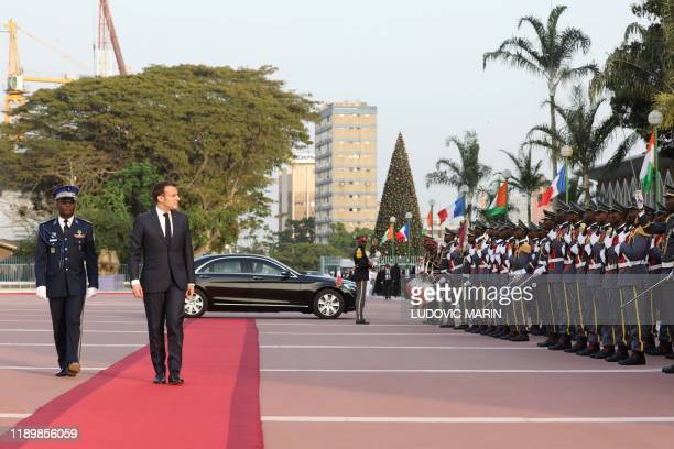 French President Emmanuel Macron inspects the honour guard as he arrive at the Presidential Palace to meet his Ivorian counterpart in Abidjan on...