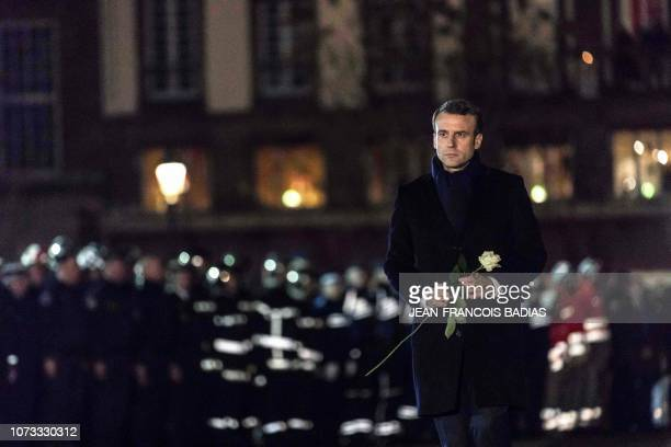 French President Emmanuel Macron is about to lay a white rose at a monument near the Christmas market in Strasbourg's Kleber square used as a...