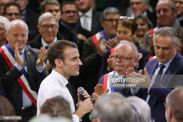 French President Emmanuel Macron is applauded at the end of a meeting gathering some 600 mayors who will relay the concerns aired by residents in...