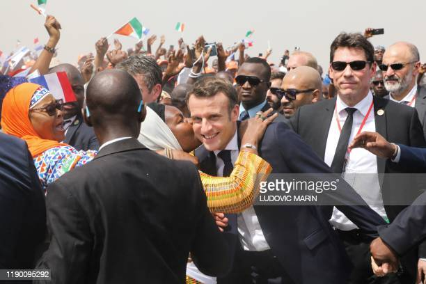 French President Emmanuel Macron is greeted as he arrives to attend a ceremony to lay the first brick of the future Bouake market, which had burnt...