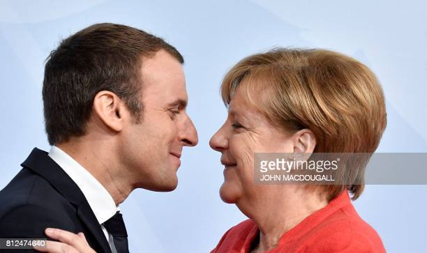 French President Emmanuel Macron is greeted by German Chancellor Angela Merkel as he arrives for a 'retreat meeting' on the first day of the G20...