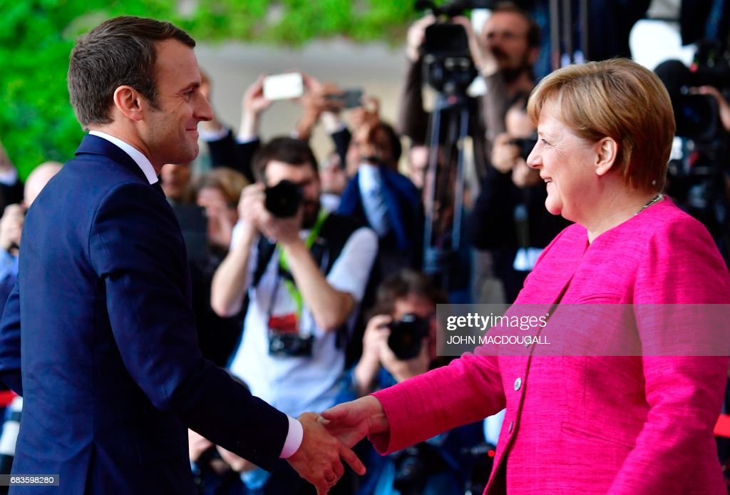 French President Emmanuel Macron (L) is greeted by German Chancellor Angela Merkel (R) prior to talks at the Chancellery in Berlin on May 15, 2017. France's new President Emmanuel Macron secured backing from key ally Chancellor Angela Merkel for his bid to shake up Europe, despite scepticism in Berlin over his proposed reforms. Travelling to the German capital to meet the veteran leader in his first official trip abroad, Macron used the opportunity to call for a 'historic reconstruction' of Europe. PHOTO / John MACDOUGALL