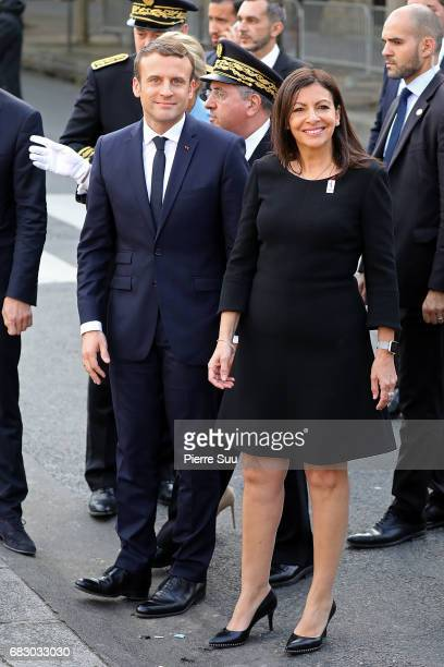 French President Emmanuel Macron is greeted by Paris Mayor Anne Hidalgo as he arrives at the City Hall for an official ceremony after his formal...