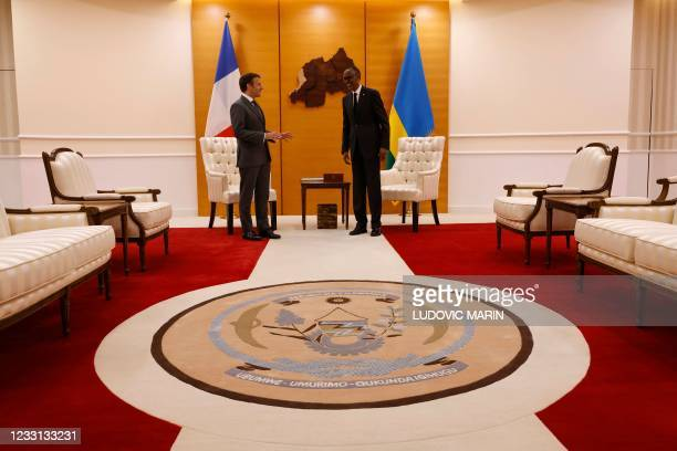 French President Emmanuel Macron is greeted by Rwandan President Paul Kagame at the Presidential Palace prior to their bilateral meeting in Kigali on...