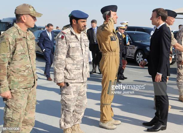 French President Emmanuel Macron is greeted by US Qatari and French armies' commanders upon his arrival at the alUdeid Air Base in the Qatari capital...