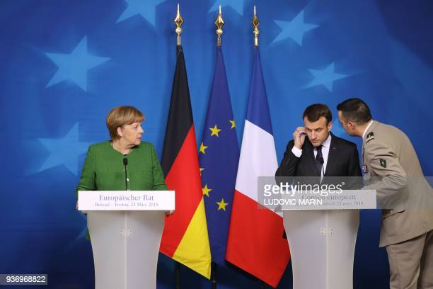 TOPSHOT French president Emmanuel Macron is informed by his security advisor about the hostage situation in Trebes during the joint press conference...