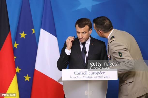 French president Emmanuel Macron is informed by his security advisor about the hostage situation in Trebes during a joint press conference on the...