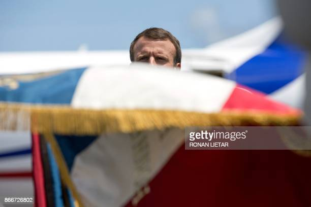 French President Emmanuel Macron is seen behind a French national flag as he is welcomed with military honours upon arrival at the start of his visit...