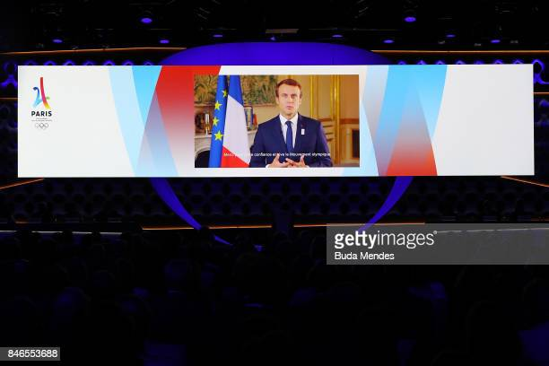 French President Emmanuel Macron is seen on the screen as he delivers a recorded message to the attendants during the 131th IOC Session 2024 2028...