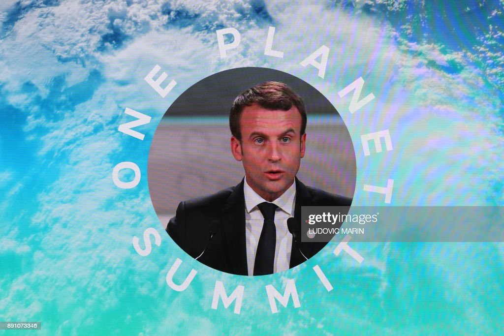 French President Emmanuel Macron is shown on a big screen as he delivers a speech at the One Planet Summit on December 12, 2017, at La Seine Musicale venue on l'ile Seguin in Boulogne-Billancourt, west of Paris. ?The French President hosts 50 world leaders for the 'One Planet Summit', hoping to jump-start the transition to a greener economy two years after the historic Paris agreement to limit climate change. /
