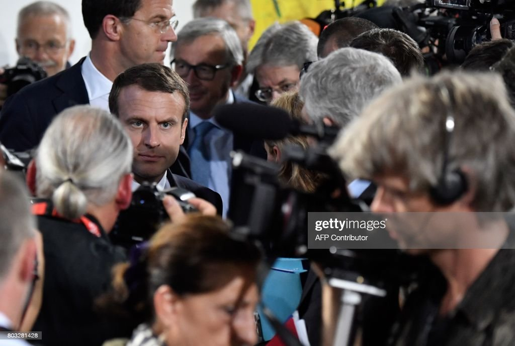 French President Emmanuel Macron (C-L) is surrounded by journalists after a press conference on June 29, 2017 at the Chancellery in Berlin following a meeting with European G20 heads of State in order to prepare the upcoming G20 summit scheduled on July 7-8, 2017. / AFP PHOTO / John MACDOUGALL