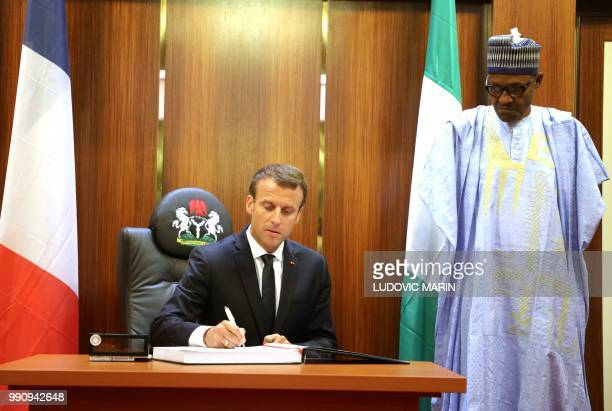 TOPSHOT French President Emmanuel Macron is watched by Nigeria's President Muhammadu Buhari as he signs the 'gold book' at The Presidential State...