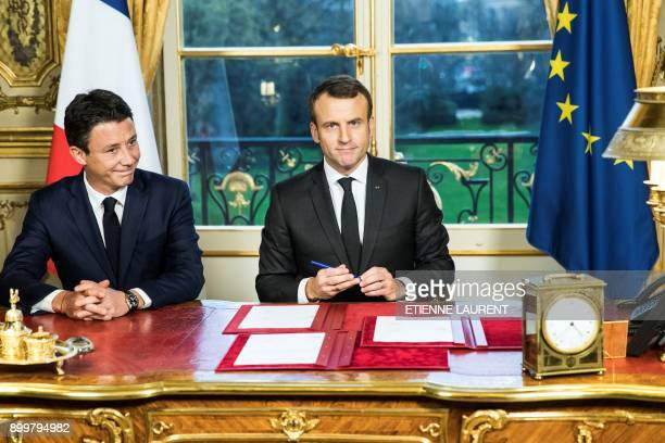 French President Emmanuel Macron is watched by the spokesperson of the government Benjamin Griveaux after signing three legal texts concerning 2018...