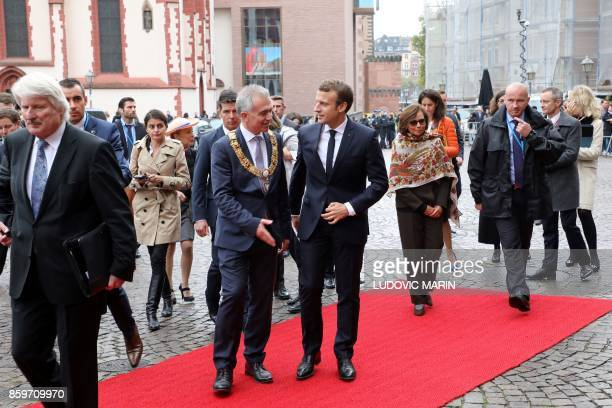 French President Emmanuel Macron is wecomed by the mayor Peter Feldmann before a welcoming ceremony at the city hall upon his arrival for a visit in...