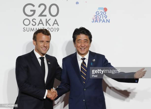 French President Emmanuel Macron is welcomed by Japanese Prime Minister Shinzo Abe before a family photo session at G20 summit on June 28, 2019 in...