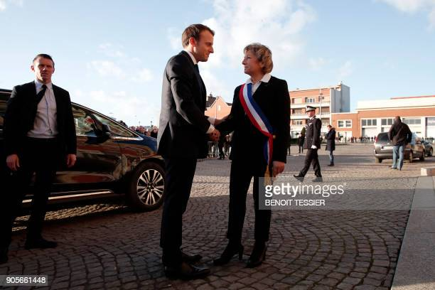 French President Emmanuel Macron is welcomed by mayor of Calais Natacha Bouchart in front of the Calais' townhall northern France on January 16 2018...