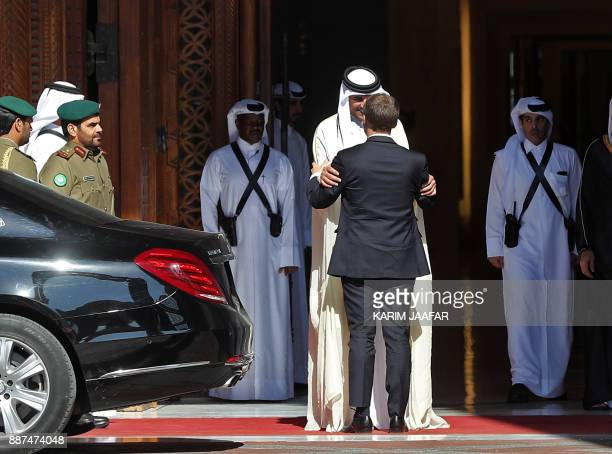 French President Emmanuel Macron is welcomed by Qatari Emir Sheikh Tamim bin Hamad alThani at the Qatari capital Doha on December 7 2017 / AFP PHOTO...