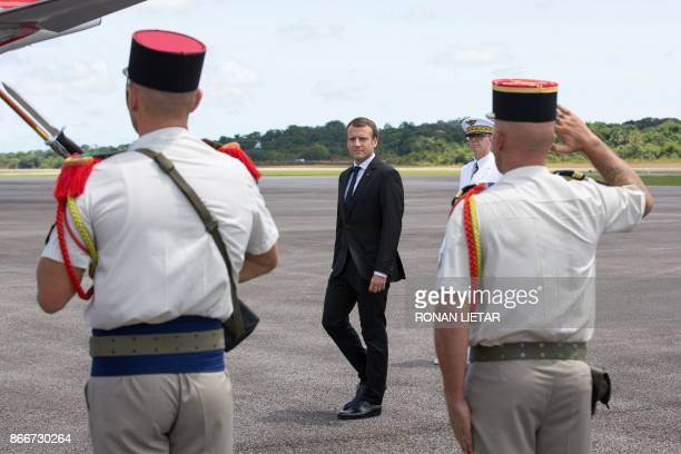 French President Emmanuel Macron is welcomed with military honours upon arrival at the start of his visit at the Felix Eboue Airport of Cayenne in...