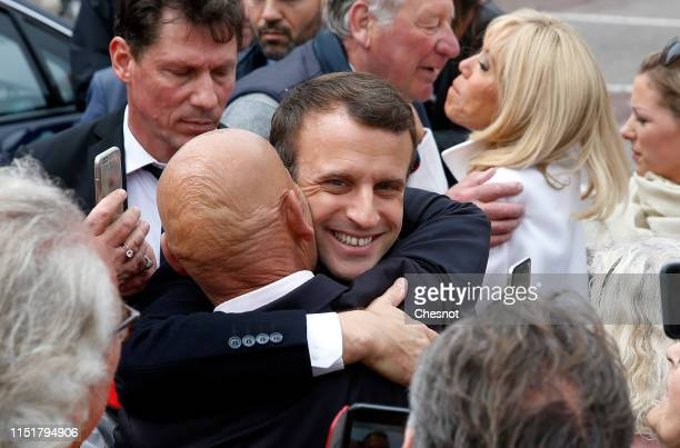 French President Emmanuel Macron kisses a supporter as he leaves the polling station after casting his vote in the European elections on May 26, 2019...