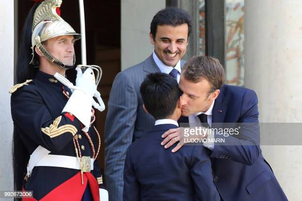 French president Emmanuel Macron kisses Hamad the son of Qatar Sheikh Tamim bin Hamad Al Thani upon arrival at the Elysee palace on July 6 in Paris