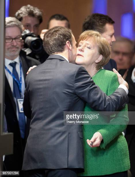French President Emmanuel Macron kisses the German Chancellor Angela Merkel at the end of the second day of an EU Summit on March 23 2018 in Brussels...