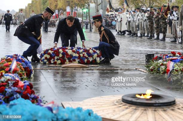 French President Emmanuel Macron lays a wreath of flowers at the tomb of the unknown soldier during a ceremony at the Arc de Triomphe in Paris on...