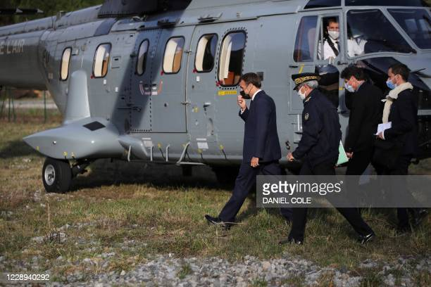 French President Emmanuel Macron leads officials as he arrives in Breil-sur-Roya, southeastern France, on October 7 during a visit in the...