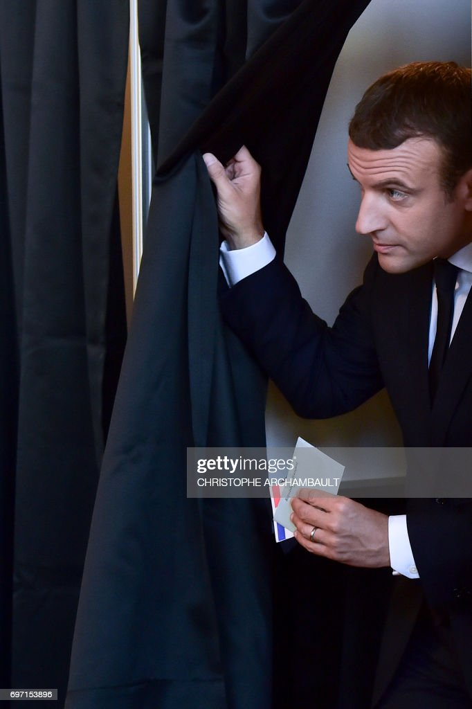 French President Emmanuel Macron leaves a polling booth with his ballot as he votes at a polling station in Le Touquet, northern France, during the second round of the French parliamentary elections (elections legislatives in French), on June 18, 2017. /