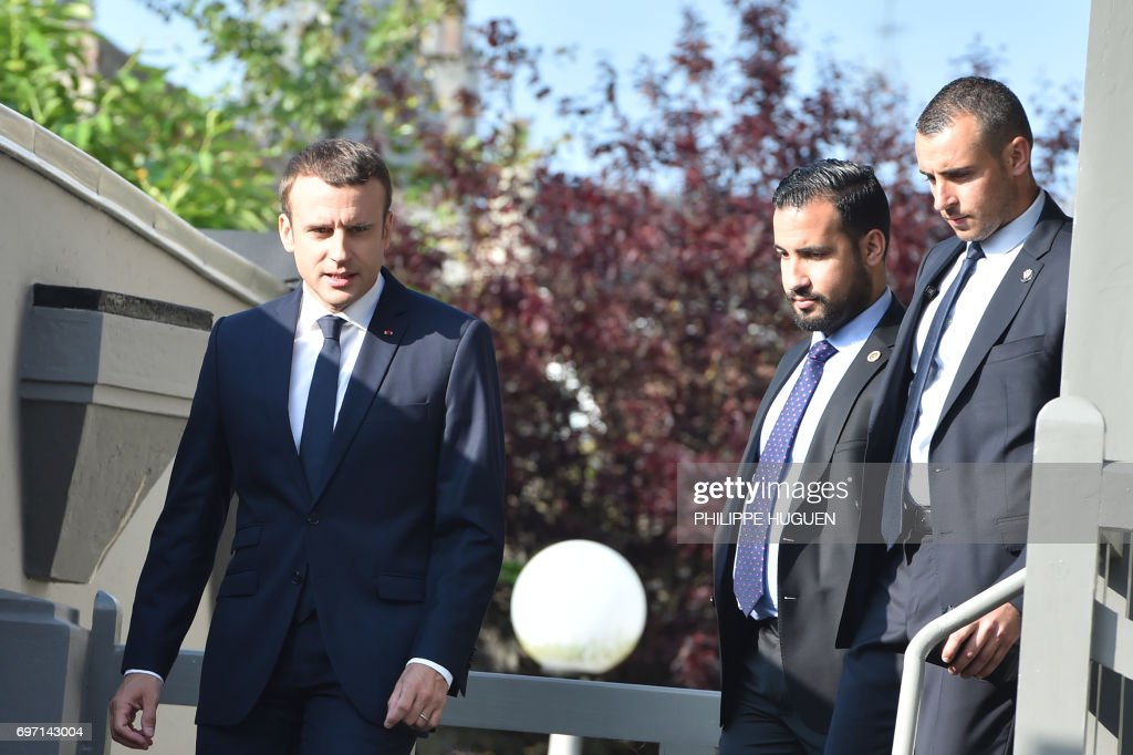 French President Emmanuel Macron (L) leaves his house to vote in Le Touquet, northern France, during the second round of the French parliamentary elections (elections legislatives in French), on June 18, 2017. / AFP PHOTO / Philippe HUGUEN