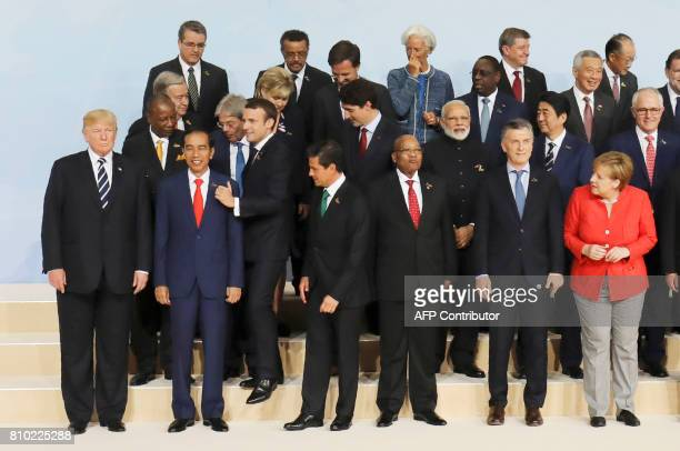 French President Emmanuel Macron leaves his position during the family picture to place himself next to US President Donald Trump as German...
