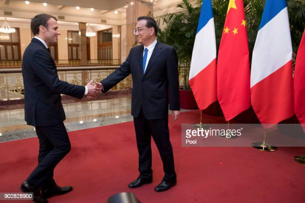 French President Emmanuel Macron left shakes hands with Chinese Premier Li Keqiang as he arrives for a meeting at the Great Hall of the People on...