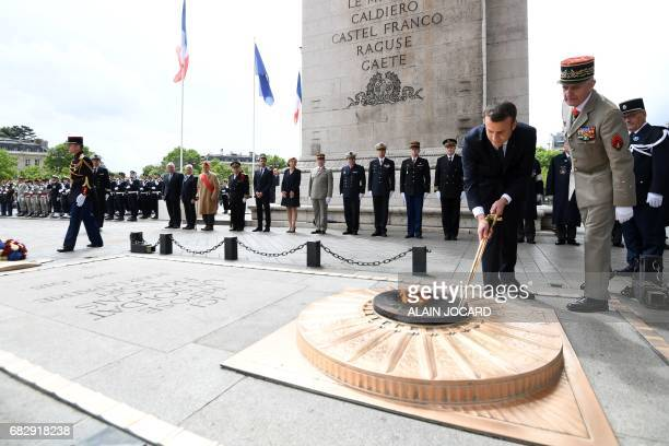 TOPSHOT French President Emmanuel Macron lights the flame at the tomb of the unknown Soldier at the Arc of Triomphe monument after his formal...