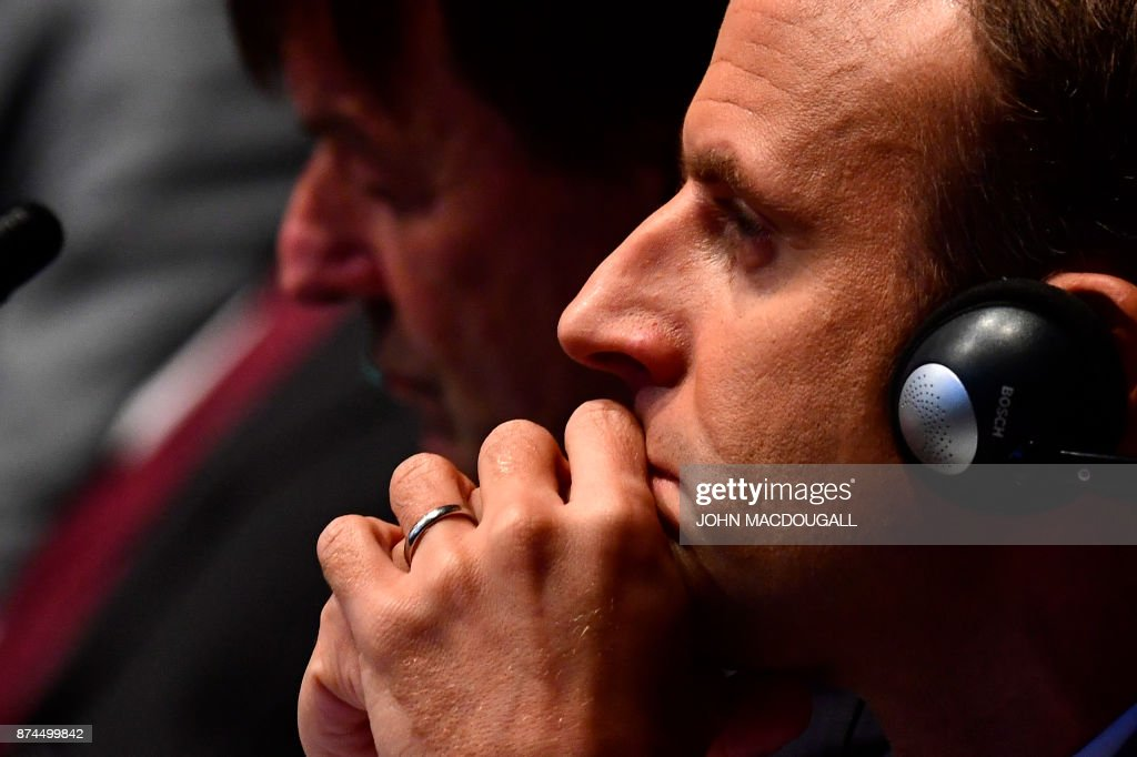 French President Emmanuel Macron listen to speeches during the UN conference on climate change (COP23) on November 15, 2017 in Bonn, western Germany. / AFP PHOTO / John MACDOUGALL