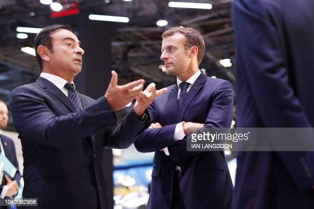 French President Emmanuel Macron listens to CEO of French car maker Renault Carlos Ghosn during an official visit at the Paris auto show in Paris on...