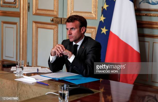 French President Emmanuel Macron listens to German Chancellor during a video conference to discuss a joint plan to spur the EU's recovery from the...